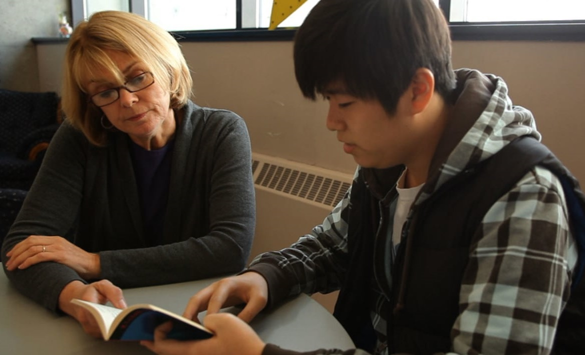 A tutor helps a student work on some problems.